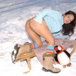 Cute nude model in the snow on a sled — Stock Photo