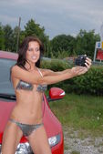 Sexy gridgirl in bikini taking selfshot pictures in front of a sportscar — Stok fotoğraf