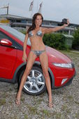Sexy gridgirl in bikini taking selfshot pictures in front of a sportscar — Stock Photo