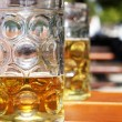 Half full beer mug in the beer garden — Stock Photo