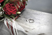 Rose bouquet with wedding rings — Stock Photo