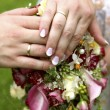 Stock Photo: Bride and groom with bouquet of lilies and wedding rings