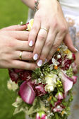 Bride and groom with bouquet of lilies and wedding rings — Stock Photo