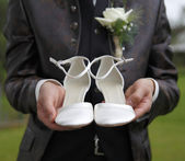 Groom is holding bridal shoes — Stock Photo