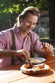 Attractive man eats traditional cheese in a Bavarian beer garden — Stock Photo