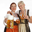 Two bavarian girls with beer in traditional costumes — Stock Photo #46597723