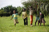 African kids help with carring palm leaves — Stock Photo