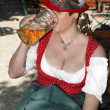 Woman in typical bavarian costume drinks beer — Stock Photo #50421717