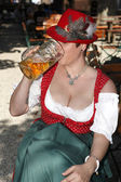 Woman in typical bavarian costume drinks beer — Stock Photo