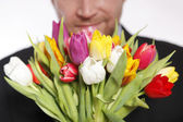 Man with a beautiful colored bouquet of tulips  — Stock Photo