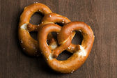 Two typical bavarian pretzel on a brown background — Stock Photo