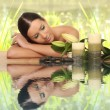 Woman relaxing in spa, with reflection on the water — Stock Photo