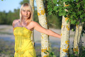 Beautiful girl in a yellow sundress around tree trunks — Stock Photo