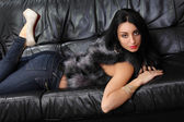 Beautiful brunette lying on a leather couch — Foto Stock