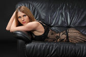Girl on the couch in sexy lingerie and mantle — Stock Photo