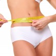 Young and sexy woman measuring her waist isolated over white background — Stock Photo