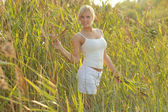 Sexy young woman in a white in the grass — Stock Photo