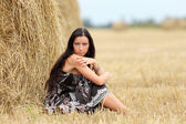 Portrait of a girl in a field with hay — Stock Photo