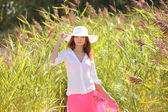 Girl in a hat on a background summer landscape — Stockfoto
