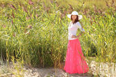 Girl in a hat on a background summer landscape — Stock Photo