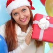 Beautiful girl in a white sweater holding gifts — Stock Photo #40813359