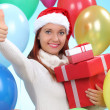 Happy girl in red Santa hat holding gift box — Stock Photo