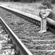 Stock Photo: Upset girl sitting on rails