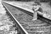 Upset girl sitting on the rails — Stock Photo