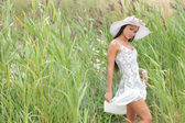 Young woman in a white dress on a background of tall grass — Stock Photo