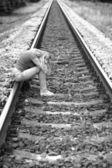 Raylar üzerinde oturan üzgün kız — Stok fotoğraf