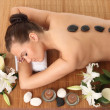 Spa. picture of woman in spa salon with hot stones — Stock Photo #40820379