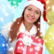 Beautiful girl dressed as Santa with a gift box — Stock Photo #40821571