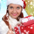 Beautiful girl dressed as Santa with a gift box — Stock Photo #40821707