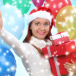 Beautiful girl dressed as Santa with a gift box — Stock Photo #40821721