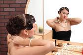 Girl gets makeup near mirror — Stock Photo
