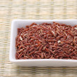 Foto Stock: Red jasmine rice in white square bowl on reed mat