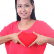 Young woman holding a heart shaped red pillow, isolated on white — Stock Photo #36939173