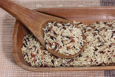 Mixed rice in wooden spoon and tray on cloth mat — Stock Photo