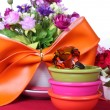 Topaz ring in a bowl with colorful artificial flower — Stock Photo
