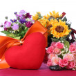 Red heart with colorful artificial flower — Stock Photo