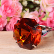 Topaz ring on wood with colorful artificial flower — Stock Photo