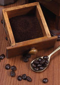 Roasted coffee beans and ground coffee in spoon on wooden backgr — Stock Photo