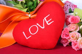 Red heart with colorful artificial flower - Close up — Stock Photo