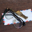 Stock Photo: Group of objects on wooden desk. Glasses, watch, envelope and pe
