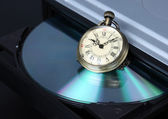 Time concept, old watch with open DVD tray — Stock Photo