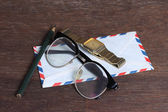 Group of objects on wooden desk. Glasses, watch, envelope and pe — Stock Photo