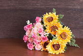 Colorful artificial flower on wood background — Stockfoto