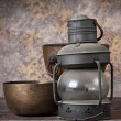 Old rusty kerosene lamp with copper bowl on wood background. — Stock Photo