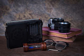 Group of objects on wood table. hourglass, key, retro radio, cam — Stock Photo