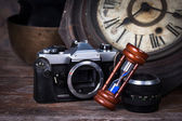 Group of objects on wood table. antique wooden clock, hourglass, — Stock Photo